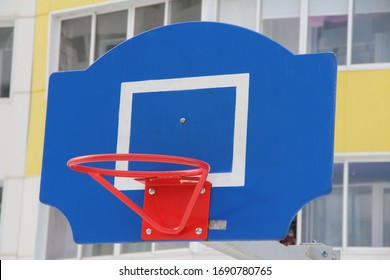 Red basketball hoop on a blue backboard on a sports field on a street in the city.