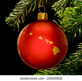 A red bauble with the golden shape of  Hawaii hanging on a christmas tree isolated on black.(series)