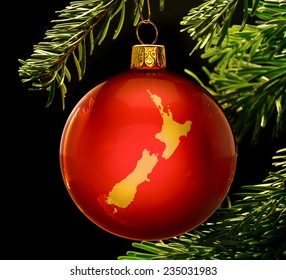 A red bauble with the golden shape of  New Zealand hanging on a christmas tree isolated on black.(series)