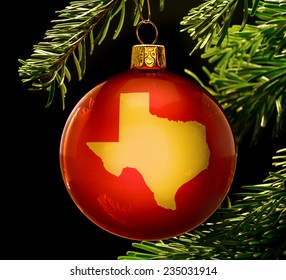 A red bauble with the golden shape of  Texas hanging on a christmas tree isolated on black.(series)