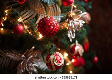 Red baubles hanging from a decorated Christmas tree