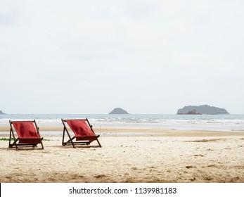 Red beach beds on calm summer beach.