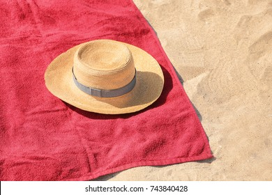 Red beach towel and hat on sand