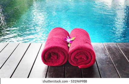 Red beach towel on the background of the pool.