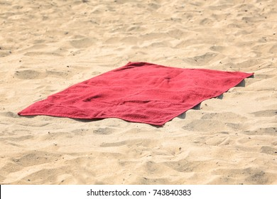 Red beach towel on sand