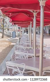 Red beach umbrellas line.
