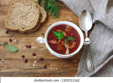 red bean soup with smoked bacon in a white bowl, vintage spoon, spicy herbs, bread, canvas towel on wooden table, rustic style