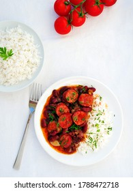 Red beans and rice with sausage over white table, vertical, flat lay