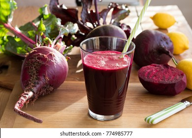 Red beet juice in a glass on a wooden table with fresh beets and lemons in the background