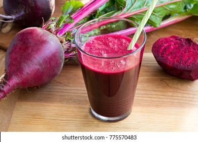 Red beet juice in a glass on a wooden table, with fresh beets in the background