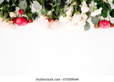 Red and beige rose flowers, eringium flower, eucalyptus branches and leaves on white background. Flat lay, top view. Floral background