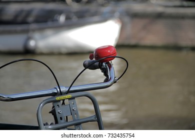 Red bell, bikes parked beside a canal in Amsterdam.