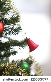 red bell on christmas tree in vertical image