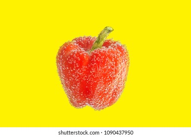 red bell pepper with bubbles of soda on a yellow background