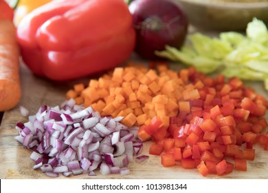 Red bell pepper, carrots and onions diced on a cutting board.
