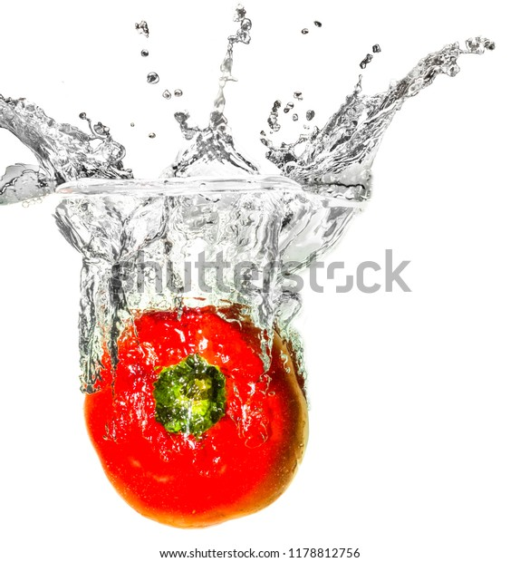 Red bell pepper dropped into liquid creating creative splash