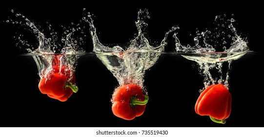 Red bell pepper falling in water with splash on black background.