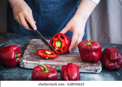 Red bell peppers. Person chopping red bell peppers. Stuffed bell peppers recipe.