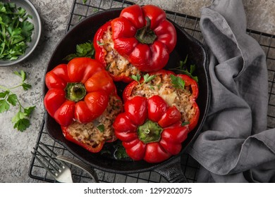 red bell peppers stuffed with meat, rice and vegetables on cast iron pan, top view