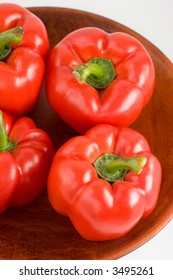 Red Bell Peppers in a wooden bowl