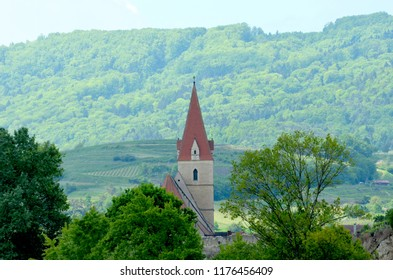 The red bell tower and steeple of a church stand out against a green background of trees, vineyards and a hill covered in forest. The sky is blue.