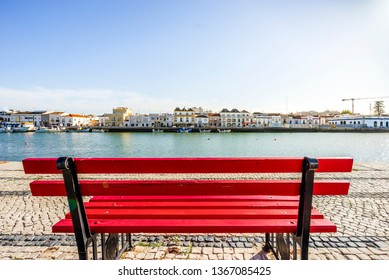 Red bench by Gilao river bank in charming Tavira, Algarve, Portugal
