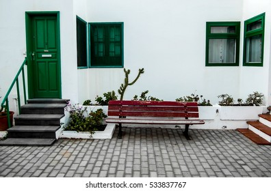 red bench in front of the wall and green door