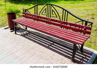 red bench in public city park on sammer day
