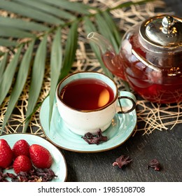 Red berries and herbal Tea, glass teapot of drink, dry hibiscus or chinese rose frowers and fresh strawberries on rustik background. Clay cup and saucer on wooden table. Tea time. Soft focus.