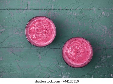 red berry fruit smoothies in glasses on a gray concrete background. view from above. copy space
