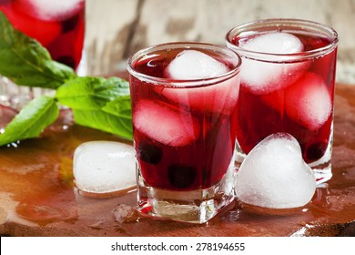 Red berry juice with ice in the shape of hearts, selective focus