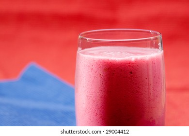 A red berry smoothie isolated on blue and red