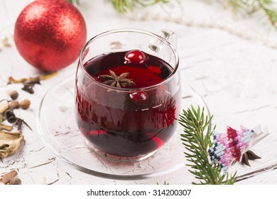 Red berry tea with cranberry and spices on white wooden table. Xmas or new year decorated background. Selective focus