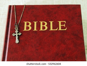 Red Bible book and a metal cross with Jesus on a chain