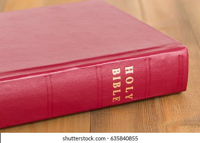 Red bible book on wooden table