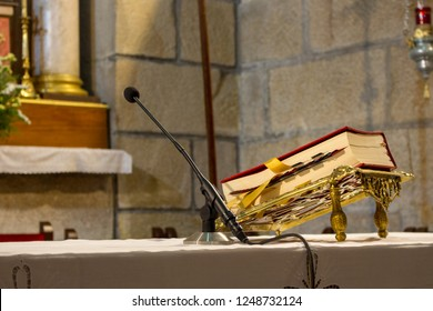 Red Bible on altar table with microphone. Faith and religion concept. Preaching background. Church interior. Lord's table concept. Holy holidays and Christmas concept. Christianity tradition.