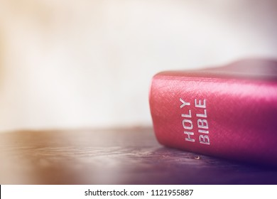 Red bible on wood desk with copy space.