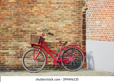Red bicycle against brick wall in Brugge, Belgium