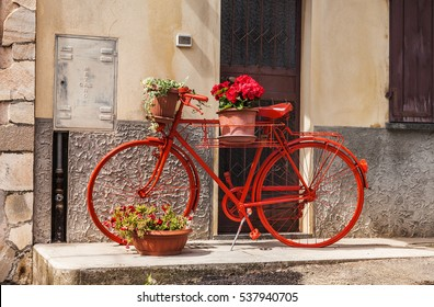 Red Bicycle with flower pots standing against the wall