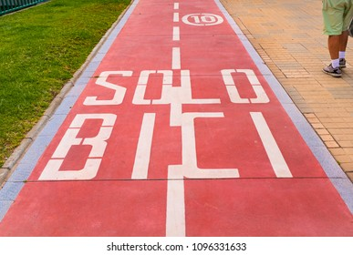 Red bicycle lane in Spain. Saying Solo Bici, Only Bikes at a max speed of 10 Kmph. There is a man walking in shorts next to the path