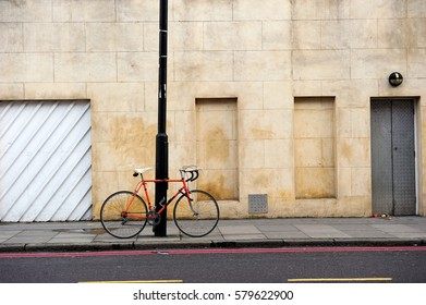 Red bicycle locking with street lamp in front of cement wall in Shoreditch area, London