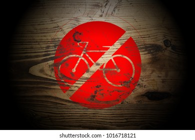 red bicycle ride forbidden sign painted on dark gold and brown wood texture background