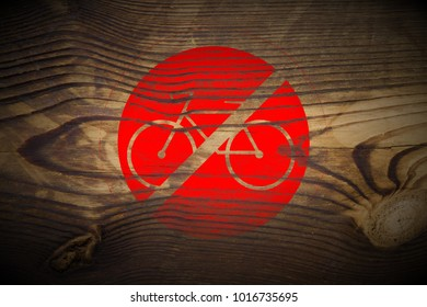 red bicycle ride forbidden sign painted on dark brown wood texture background