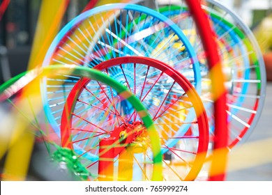 Red bicycle rim seen through colorful bike wheels and spokes in the foreground and background