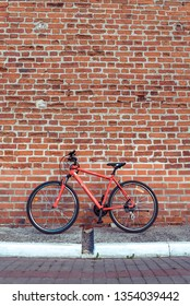 A red bicycle in the summer in the city stands parked against a brick old wall. Free space for text. The concept of parking, walking, repair, bike wheels and a frame with a wheel.