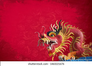 red big dragon statue on red texture background with copy space.