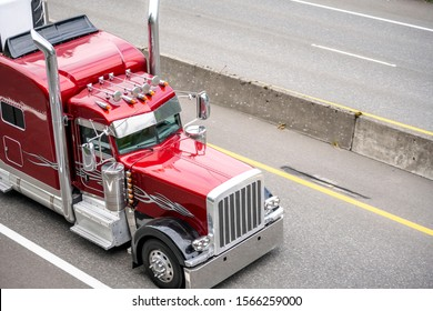 Red big rig classic American bonnet semi truck with high vertical chrome exhaust pipes and visor transporting commercial cargo in refrigerator semi trailer driving on the turning road with trees
