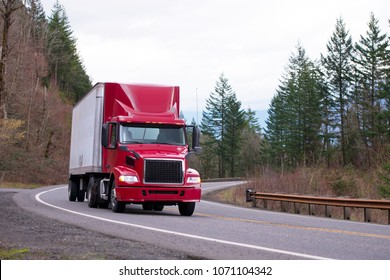 Red big rig day cab semi truck with aerodynamic spoiler on the roof transport dry van semi trailer running on winding road with trees and safety fence on the shoulder