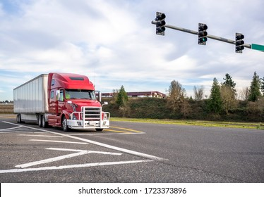Red big rig diesel long haul semi truck with powerful aluminum grille guard transporting commercial cargo in dry van semi trailer standing on the crossroad intersection with traffic light