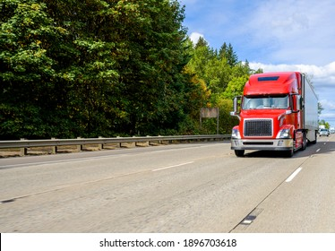 Red big rig industrial grade bonnet long hauler diesel semi truck with high roof cab and refrigerator semi trailer running with commercial cargo on the wide highway road with green trees hillside